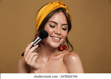 Close up beauty portrait of an attractive lovely young topless woman wearing headband standing isolated over brown background, holding makeup blusher brush