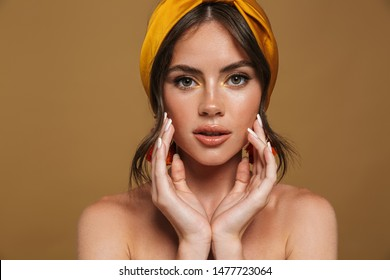 Close up beauty portrait of an attractive young topless woman wearing headband standing isolated over brown background, posing, touching her face