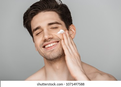 Close up beauty portrait of half naked satisfied young man applying facial cream isolated over gray background