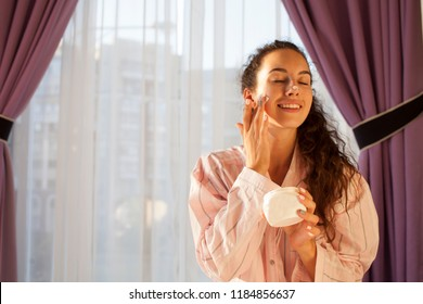 Close up beauty portrait of a laughing beautiful half naked woman applying face cream and looking away