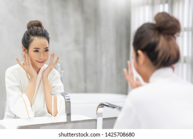Close up beauty portrait of a laughing beautiful woman applying foam for washing on her face and looking at the mirror. Skincare spa relax. Morning and night cream.
