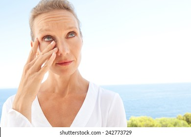 Close up beauty portrait of a senior mature healthy woman with blue eyes and flawless skin crying and drying up her tears, worried and emotional. Mature and aging face with a sad expression, outdoors.