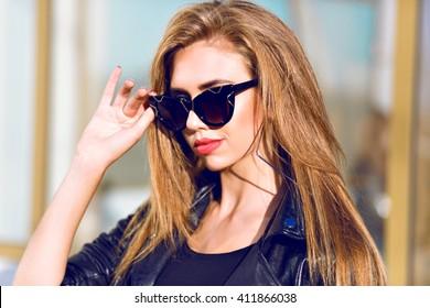 Close up beauty portrait of sexy stunning blonde woman, stylish black sunglasses, long hairs perfect skin, sunny day, black leather jacket.