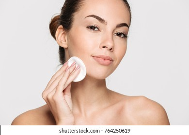 Close up beauty portrait of a young attractive woman cleaning her face with a cotton pad isolated over white background