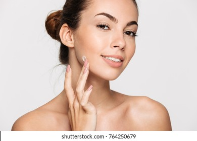 Close up beauty portrait of a young beautiful half naked woman applying face cream and looking at camera isolated over white background