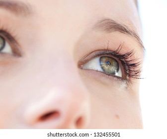 Close up beauty portrait of a young caucasian healthy woman face and eye looking up with long eyelashes.