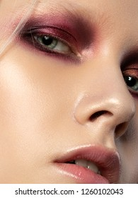 Close up beauty portrait of young woman with coral red smokey eyes. Perfect skin and fashion makeup. Studio shot. Sensuality, passion, trendy youth makeup concept.