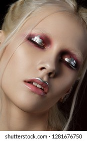 Close up beauty portrait of young woman with red and silver make up. Perfect skin and fashion make up. Studio shot. Sensuality, passion, trendy youth makeup concept.