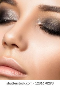 Close up beauty portrait of young woman with dark golden smokey eyes makeup. Perfect skin and fashion makeup. Studio shot. Sensuality, passion, trendy luxurious makeup concept.