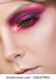 Close up beauty portrait of young woman with purple smokey eyes. Perfect skin and fashion makeup. Studio shot. Sensuality, passion, trendy youth makeup concept. Extreme closeup, partial face view