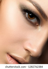 Close up beauty portrait of young woman with golden makeup. Perfect skin and fashion makeup, smokey eyes. Studio shot. Sensuality, passion and skincare concept. Extreme closeup, partial face view