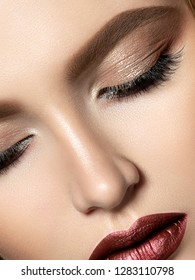 Close up beauty portrait of young woman with dark red lips and brown smokey eyes makeup. Perfect skin and beautiful makeup. Studio shot. Extreme closeup, partial face view
