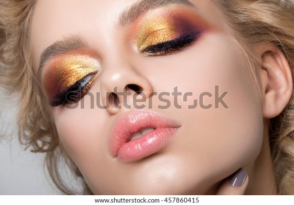 Close up beauty portrait of young woman with beautiful summer bright makeup. Modern smokey eyes with colorful metallic eyeshadows. Studio shot