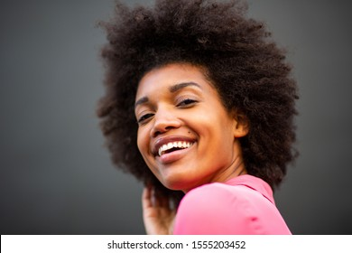 Close up beauty side portrait of young african american woman smiling against gray background
