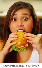 Close up of a beauty woman in cafe eating a delicious hamburger