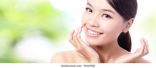 close up of Beauty woman Face and hand touch her face with green background, model is a beautiful asian girl