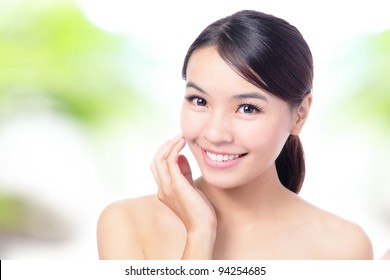 close up of Beauty woman Face and hand touch her face with green background for skin care concept, model is a beautiful asian girl