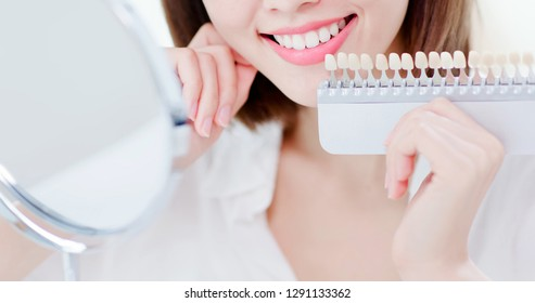 close up of beauty woman look her beautiful teeth in the mirror and check the color of the tooth