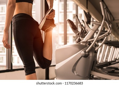 Close up beauty woman stretching legs in workout fitness gym center with sport equipment and treadmill background. Sporty girl warming up before exercise training. Lifestyle and healthy people concept