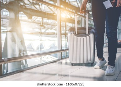 Close up of beauty woman traveling and holding trolley suitcase in airport. People and Lifestyles concept. Travel around the world theme. Adventure and business trip theme. Front and lower angle