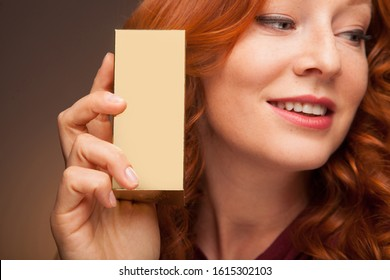 A close up of a beautyful woman with red hair holding a small gold box with perfume or cream. Photo in studio on brown background