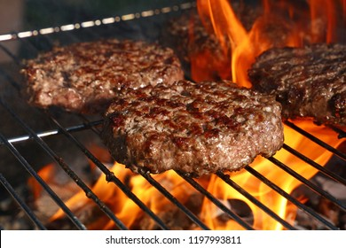 Close up beef or pork meat barbecue burgers for hamburger prepared grilled on bbq fire flame grill, high angle view