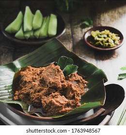 Close up of Beef Rendang, Indonesian traditional food from Padang, West Sumatra. The dish is arranged among the spices and herb used in the recipe.