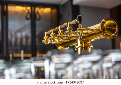 Close up of a beer faucet or tap with huge arrenge of an empty glasses in the bar or pub, restaurant concept