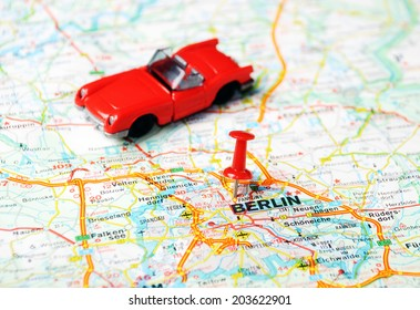 Close up of Berlin map with red pin an a cabrio - Travel concept