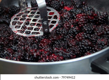 Close up of berries being mashed for jam
