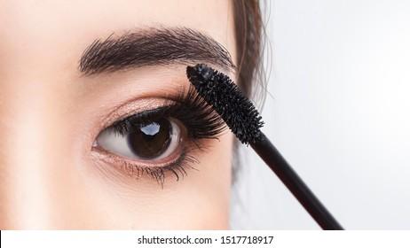 Close up beside applying mascara brush on eyelash. Applying cosmetic make up eyelash Extensions. Asian eye make up cosmetics.