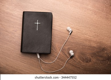 Close up of a Bible connected with earphones