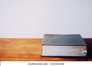 Close up of bible on wood table over white wall background, Christian faith and education or devotional concept with copy space