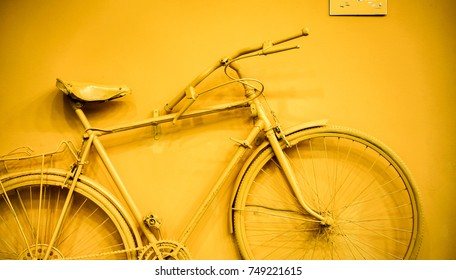 close up of bicycle as decoration on the wall. old painted bicycle attached to the wall in art office toned to yellow golden color. vintage bicycle on decorative color wall