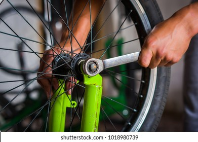 Close up of bicycle mechanic in a workshop in the repair process of the wheel with a wrench