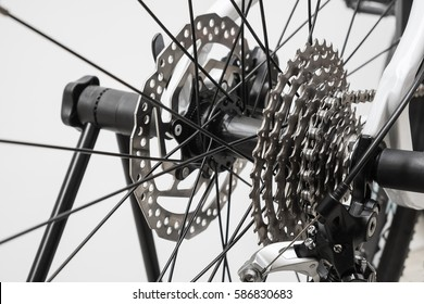 Close up of a Bicycle wheel with details, chain and gearshift mechanism with lighting effect.