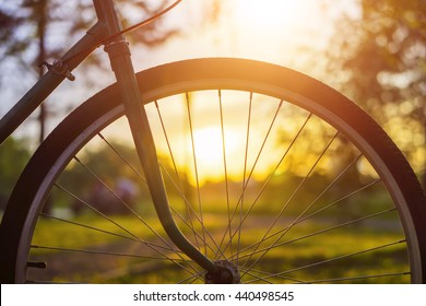 Close up of bicycle wheel with sunset on blurred background