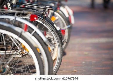 Close up of bicycles wheels parked in a row in the city, blurred background and copy space.