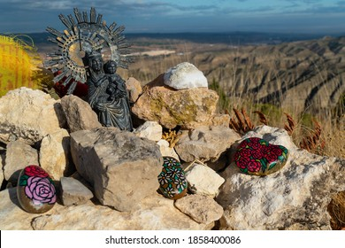 Close up of the big landmark on top of Cabezo del Sillon with a Virgin del Pilar, offerings and Buddhist flags in Maria de Huerva, Zaragoza, Spain