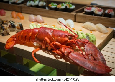 close up of big lobster on wood tray with sushi