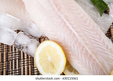 Close up of Big slice of fish raw food with lemon and green leaf