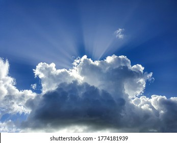 CLOSE UP Big white and grey cumulus cloud completely covers the summer sun shining down on earth. Few bright rays of sun shine past a massive cloud drifting over the clear blue sky. Idyllic cloudscape