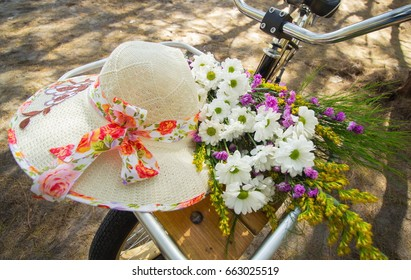 Close up of bikes carrying hat and bucket of flowers