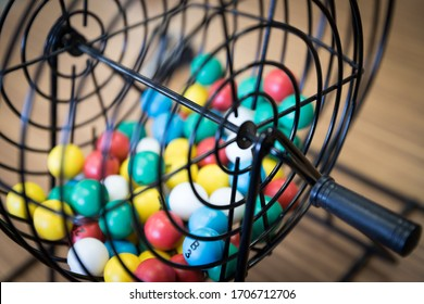 A close up of a bingo cage filled with multi-colored balls. Each ball has a letter and number on it that corresponds to a number on the player's bingo card. Bingo is a game of chance.