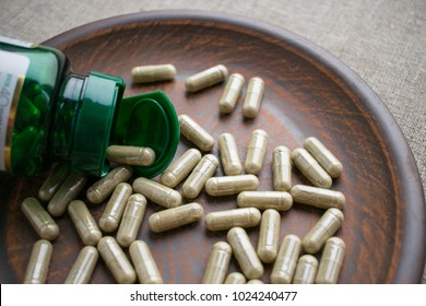 Close up biotin capsules and bottle on clay brown plate on burlap background. Dietary supplements for healthy  skin, hair, nail. Vitamins and minerals for vegans and vegetarians. Superfood