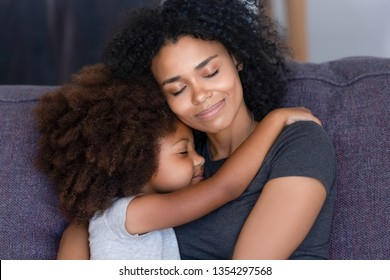Close up biracial family portrait loving mother and little daughter sitting on couch at home hugging with closed eyes. Love, new mom for adopted child, warm relationships, caring elder sister concept - Shutterstock ID 1354297568