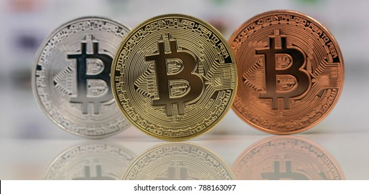 Close up of Bitcoins, gold bitcoin, silver bitcoin and bronze bitcoin with blurred background of world flags. reflection of the bitcoins visible.