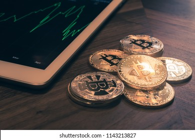 Close up Bitcoins on wooden table, tablet show green stock graph beside with dark room light, vintage retro style. Business concepts for cryptocurrency, digital money exchange and fund investment.