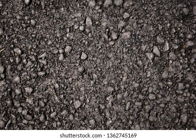Close up of black asphalt with colored stones. Rough surface. Abstract texture background