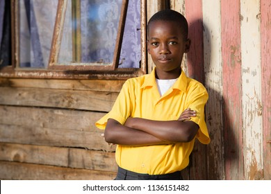 Close up of a black boy with his arms crossed while he is looking straight into the camera